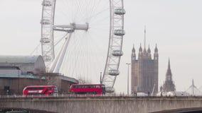 Los autobuses van más allá de London Eye y de Ben On Waterloo Bridge grande almacen de metraje de vídeo