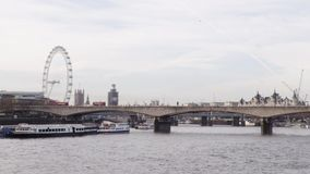 Los autobuses van más allá de London Eye y de Ben On Waterloo Bridge grande almacen de video