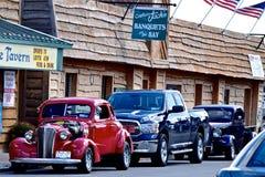 Los automóviles clásicos alinean la calle de esta pequeña ciudad del rastro de la vía marítima en NY Foto de archivo libre de regalías