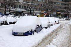Los automóviles se cubren con una nieve estacionada en la calle Imagen de archivo libre de regalías