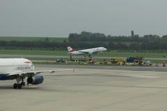 Los aviones de British Airways en la pista y Austrian Airlines ventilan Imagenes de archivo