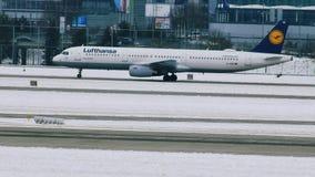 Los aviones de Lufthansa se mueven en el aeropuerto de Munich, invierno con nieve almacen de metraje de vídeo
