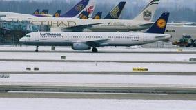 Los aviones de Lufthansa se mueven en el aeropuerto de Munich, invierno con nieve almacen de video