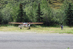 Los aviones ligeros y una motocicleta parquearon cerca de la pista de aterrizaje foto de archivo