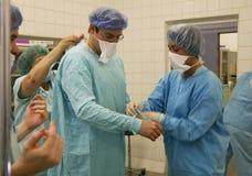 Los ayudantes visten al cirujano b Imagen de archivo