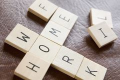 Los azulejos de madera en crucigrama forman las palabras Hom del deletreo Foto de archivo
