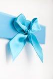 Los azules turquesa bonitos arquean y cinta en una caja de regalo Fotografía de archivo