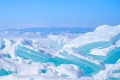 Los azules turquesa hermosos grandes hielan en el lago Baikal congelado con las montañas en el fondo imagenes de archivo