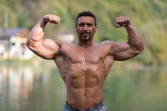 Los bíceps dobles presentan al aire libre fotos de archivo libres de regalías