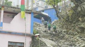 Los Backpackers caminan al pueblo en el viaje del circuito de Manaslu almacen de metraje de vídeo
