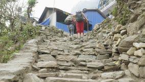 Los Backpackers caminan al pueblo en el viaje del circuito de Manaslu almacen de video