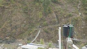 Los Backpackers caminan en puente colgante en el viaje del circuito de Manaslu almacen de video