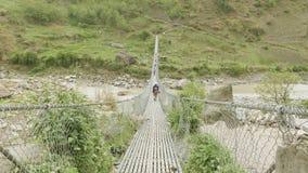 Los Backpackers caminan en puente colgante sobre el río en Nepal Viaje del circuito de Manaslu almacen de video