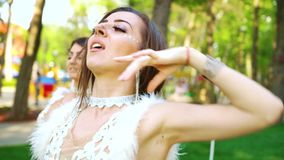 Los bailarines de sexo femenino atractivos en trajes del encanto se realizan en parque soleado almacen de metraje de vídeo