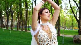 Los bailarines de sexo femenino en trajes lujosos y velos nupciales se realizan en parque de la ciudad almacen de metraje de vídeo