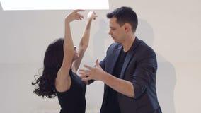 Los bailarines flexibles bailan danzas de salón de baile en un cuarto brillante con las pequeñas ventanas almacen de metraje de vídeo