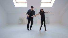 Los bailarines flexibles bailan danzas de salón de baile en un cuarto brillante con las pequeñas ventanas almacen de video