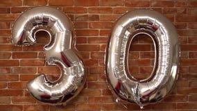 Los 30 balones de aire felices del cumpleaños agitan en un fondo del ladrillo metrajes