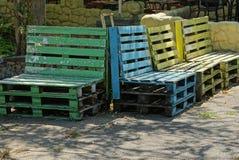 Los bancos de madera coloreados de plataformas están en el asfalto imagenes de archivo