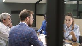 Los banqueros americanos étnicos combinan trabajan, las negociaciones en el escritorio en compañía multiétnica almacen de video