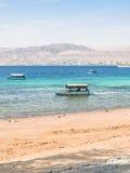 Los barcos acercan a la playa de Aqaba y a la vista de la ciudad de Eilat Imagenes de archivo