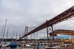 Los barcos amarraron debajo del puente de 25 de Abril en Lisboa Foto de archivo
