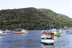 Los barcos de la pesca y del turismo atracaron en el embarcadero en varios tamaños y colores en la costa de São Pablo fotografía de archivo libre de regalías