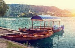 Los barcos de madera en el lago sangraron en Eslovenia en el fondo de la isla y del castillo Fotografía de archivo