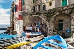 Los barcos de madera se amarran en la costa de la ciudad de Riomaggiore en el parque de Cinque Terre National, Italia Imágenes de archivo libres de regalías