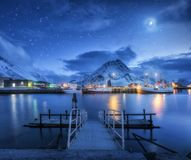 Los barcos de pesca acercan al embarcadero en el mar y a las montañas nevosas en la noche Fotos de archivo libres de regalías