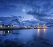 Los barcos de pesca acercan al embarcadero en el mar y a las montañas nevosas en la noche Fotografía de archivo libre de regalías