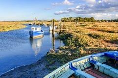 Los barcos de pesca amarraron en el río costero en la región pantanosa, East Anglia, fotografía de archivo