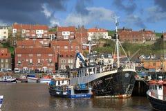 Los barcos de pesca en Whitby se abrigan, Yorkshire del norte. Fotografía de archivo