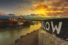 Los barcos de pesca hunker abajo en el puerto de Lyme Regis Imagenes de archivo