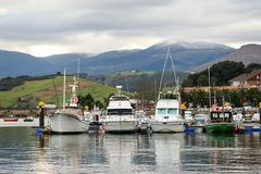 Los barcos de placer amarraron en un puerto con un fondo de la monta?a con nieve y el cielo nublado fotos de archivo