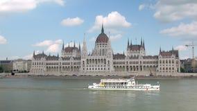 Los barcos de placer se están moviendo sobre el río Danubio delante del edificio húngaro del parlamento en Budapest metrajes