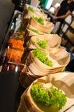 Los barcos del sushi con verde adornan Foto de archivo libre de regalías