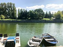 Los barcos y los catamaranes en un lago de la charca en un canal del río con agua florecida verde se amarran en la orilla imágenes de archivo libres de regalías