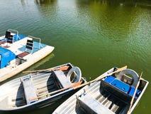 Los barcos y los catamaranes en un lago de la charca en un canal del río con agua florecida verde se amarran en la orilla fotos de archivo