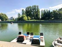 Los barcos y los catamaranes en un lago de la charca en un canal del río con agua florecida verde se amarran en la orilla fotografía de archivo libre de regalías