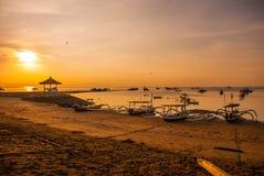 Los barcos y el pabellón tradicionales del Balinese en Sanur varan por la mañana en el amanecer, Bali, Indonesia Fotos de archivo