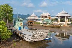 Los barcos y el transbordador de pesca amarraron en la costa en pueblo pesquero  Fotos de archivo