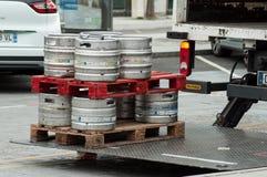 Los barriles de cerveza de Heineken del camión de reparto parquearon en la calle cerca de restaurante fotografía de archivo