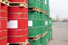 Los barriles de 200 litros de metal están en la plataforma en la calle Barriles rojos y verdes para el petr?leo, sustancias qu?mi fotografía de archivo libre de regalías