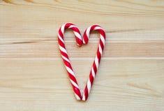 Los bastones de caramelo en corazón forman en fondo de madera Foto de archivo