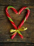 Los bastones de caramelo en un corazón forman en un fondo de madera Imágenes de archivo libres de regalías