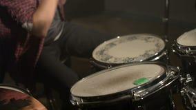Los baterías de pelo largo juegan la batería en un cuarto oscuro en un fondo negro Músico de la roca Plan estático foco hacia núm almacen de video