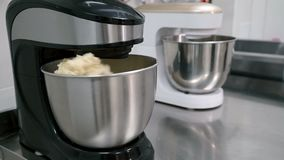 Los batidores eléctricos blancos y negros están mezclando la pasta en los potes de acero en la cocina del restaurante almacen de metraje de vídeo
