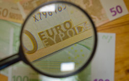 Los billetes de banco aumentaron la lupa fotografía de archivo libre de regalías