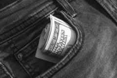 Los billetes de banco de centenares de dólares de EE. UU. se tuercen en un tubo, pegándose fuera de un bolsillo de vaqueros